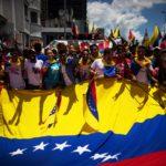 Uno scatto in cui i manifestanti si riuniscono intorno a una grande bandiera del Venezuela