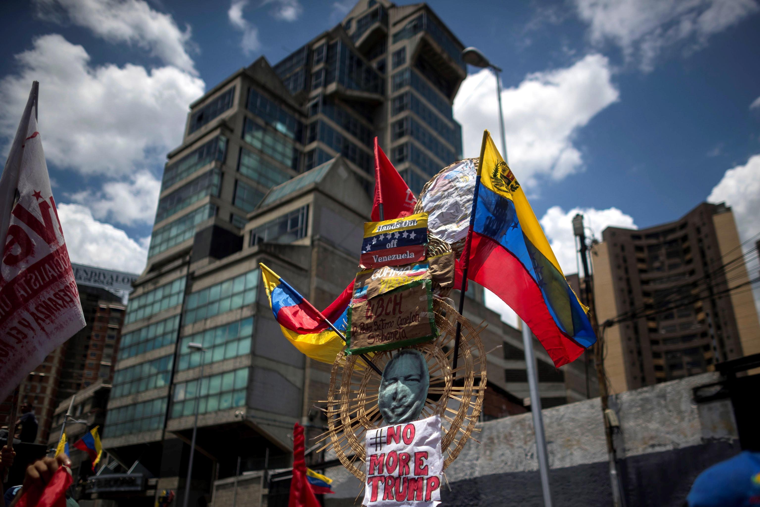 """Tra le bandiere del Venezuela, compare un cartello con scritto """"Basta con Donald Trump"""""""
