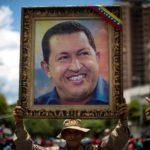 Alcuni manifestanti espongono il ritratto di Hugo Chavez, presidente del Venezuela e guida del movimento populista dal 1999 fino alla sua morte nel 2013