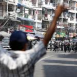 Un manifestante reagisce mentre gli agenti di polizia anti-sommossa bloccano una strada durante una protesta contro il colpo di stato militare, a Yangon, Myanmar, 26 febbraio 2021.