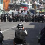 La polizia antisommossa avanza in una strada mentre i membri della stampa scattano foto durante una protesta contro il colpo di stato militare, a Yangon, Myanmar, 26 febbraio 2021.