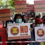 """I manifestanti tengono cartelli con la scritta """"Non abbiamo bisogno della rielezione"""" durante una protesta contro il colpo di stato militare, vicino all'Ambasciata di Thailandia a Yangon, Myanmar, il 26 febbraio 2021."""