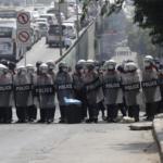 Agenti di polizia anti-sommossa bloccano una strada durante una protesta contro il colpo di stato militare, a Yangon, Myanmar, 26 febbraio 2021.