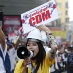 Un manifestante tiene un cartello a sostegno del movimento di disobbedienza civile (CDM) durante una protesta contro il colpo di stato militare mentre la polizia antisommossa avanza in una strada mentre le tensioni aumentano a Yangon, Myanmar, il 26 febbraio 2021.
