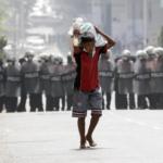 Un ragazzo trasporta un sacco di riso davanti agli agenti di polizia anti-sommossa che bloccano una strada durante una protesta contro il colpo di stato militare, a Yangon, Myanmar, 26 febbraio 2021.