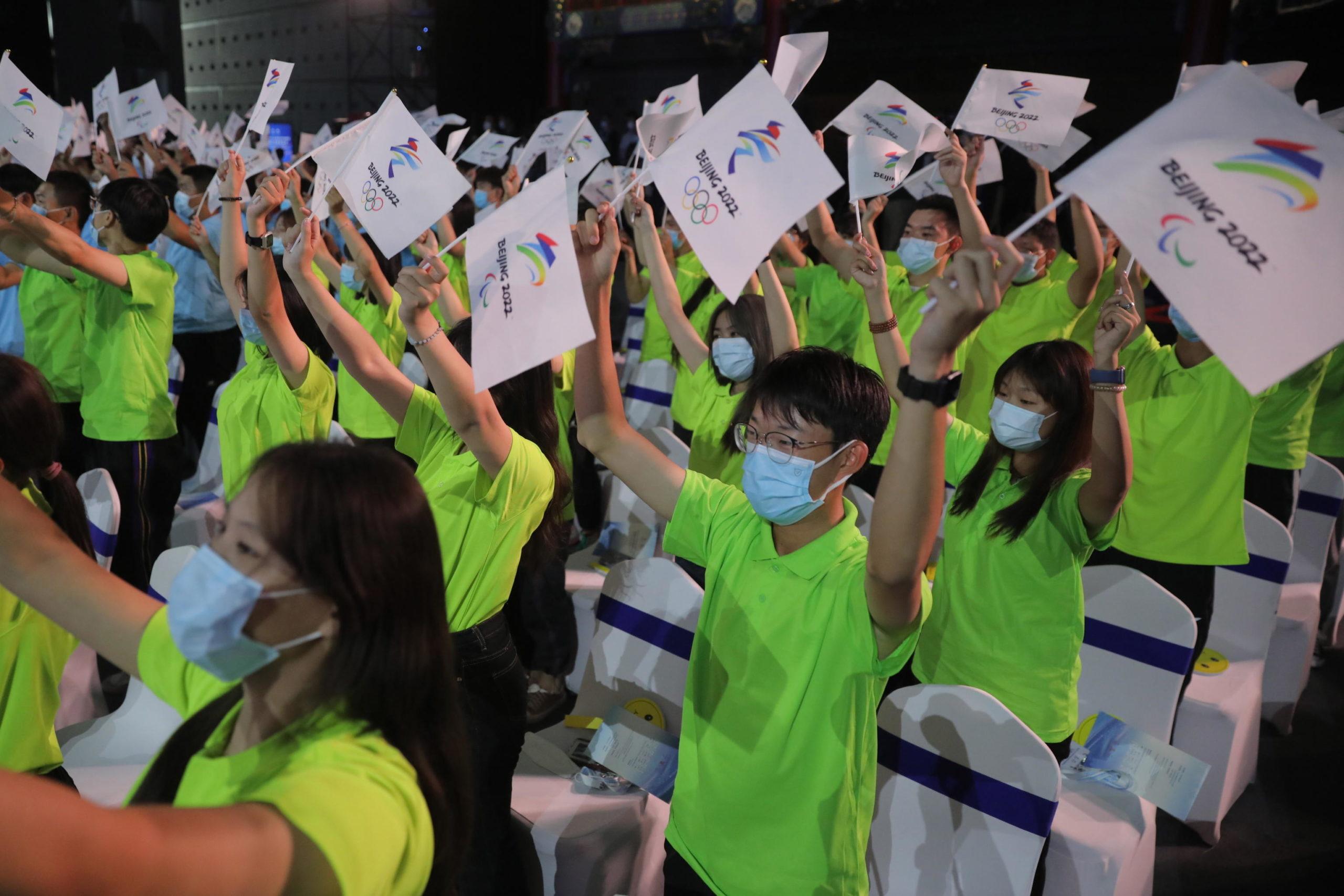 I lavoratori sventolano le bandiere con il motto dell'edizione delle Olimpiadi invernali 2022